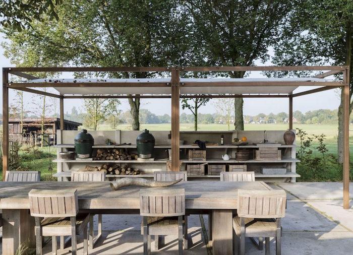 terrasse aménagée avec cuisine d'extérieur et meuble en bois et toit en toile