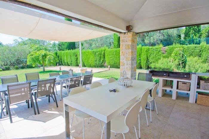 terrasse de maison ouverte et couverte sur carrelage avec cuisine extérieure et vue sur grand jardin