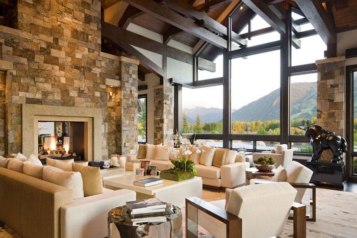 salon haut de plafond avec poutres en bois et mur en pierre de parement avec vue sur montagnes