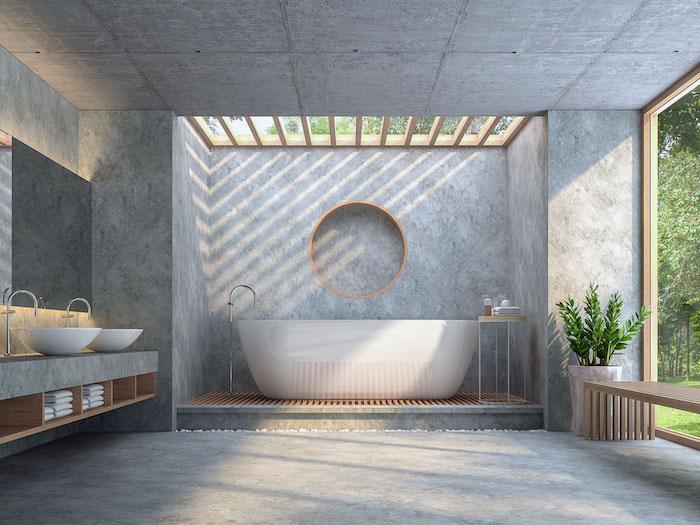 grande salle de bain ouverte avec baie vitrée sur jardin, sol murs et plafond en béton avec baignoire ilot