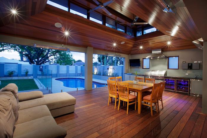 salon et cuisine d'été couverte design moderne avec sol en parquet bois avec piscine