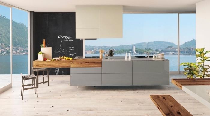 cuisine spacieuse et éclairée aux fenêtres grandes et murs blancs avec îlot tendance en gris et bois foncé