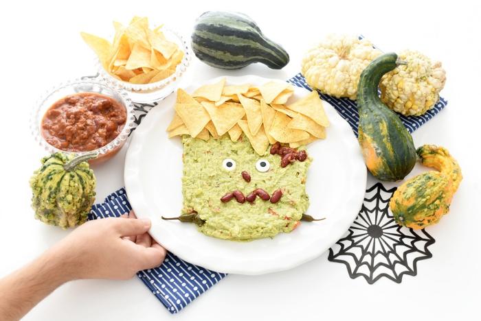 une présentation amusante d'un guacamole frankenstein d'halloween, servi avec des chips tortilla