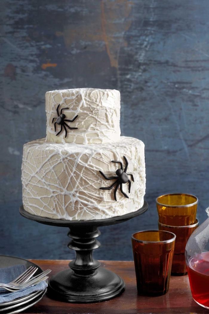 modèle de gâteau sur deux étages au glaçage blanc avec décoration en chocolat blanc design toile d'araignée, recette gateau halloween