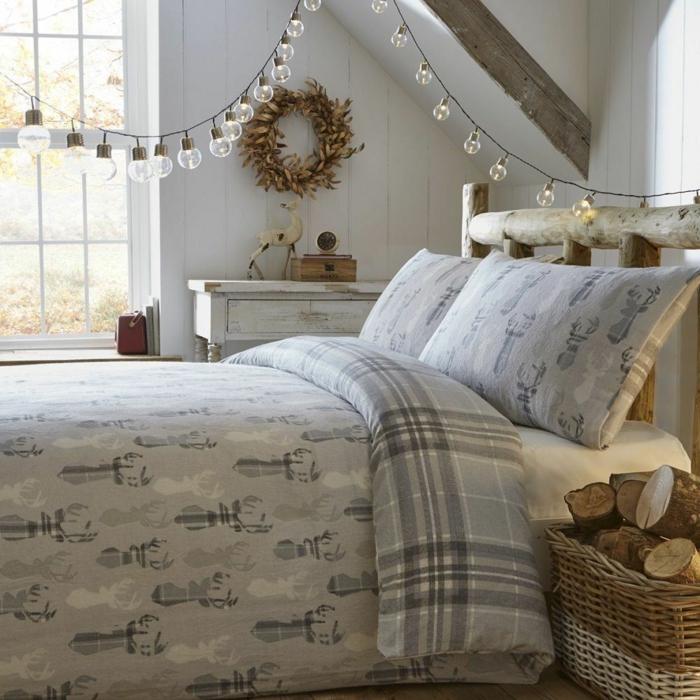 panier rustique avec des bûches dans une chambre cosy, guirlande d'ampoules, housse de couette cocooning, tête de lit en bois