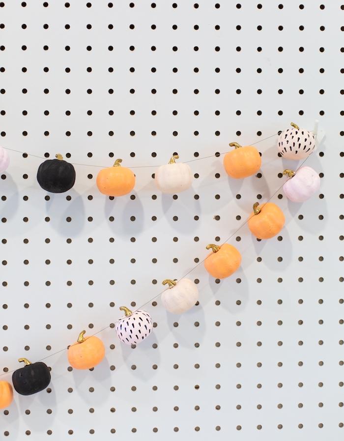 décoration halloween a fabriquer, guirlande halloween de potirons décoratifs décorés à motifs variés enfilés sur un fil