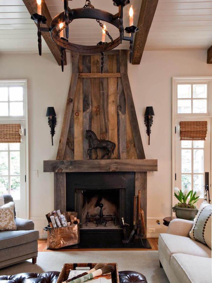 modele habillage cheminée ancienne avec manteau et conduit en bois ancien type déco de chateau moyen age, poutre apparentes et chandelier en métal vintage