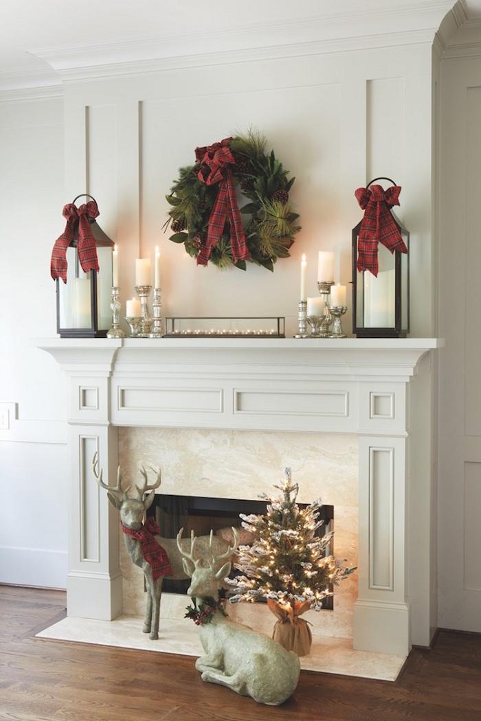 habillage cheminée ancienne déco de noel avec lanternes bougies couronne végétale et statues renes