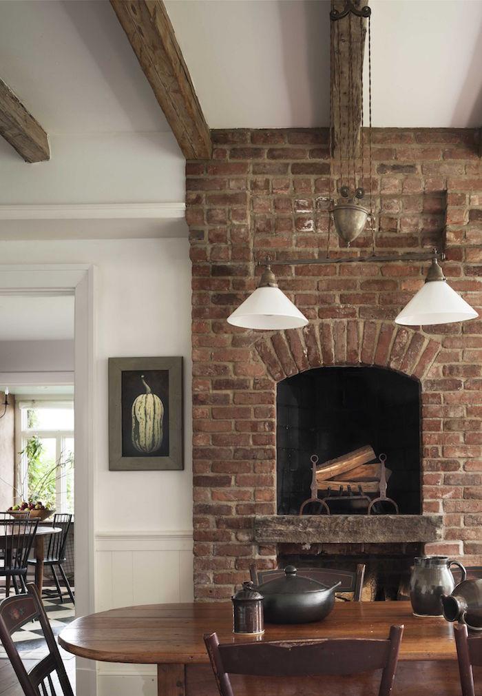 cheminée haute type four à bois en briques rouges anciennes jusqu'au plafond blanc avec poutre en bois