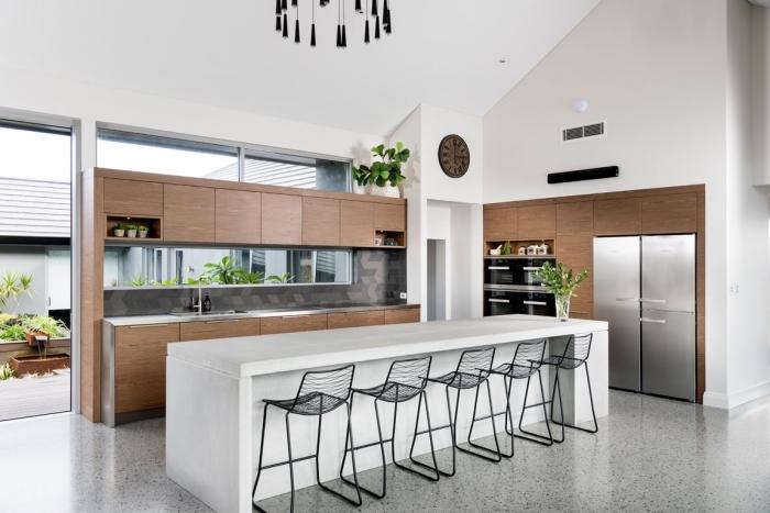 cuisine ilot central moderne avec meubles en bois foncé et finitions en noir, exemple de design intérieur stylé tendance moderne