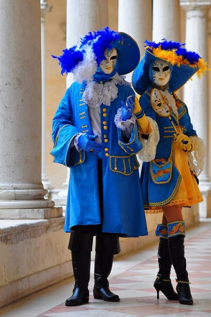 couple en bleu portants des masques vénitiens, grands chapeaux de carnaval, longues bottes noires, piliers blancs