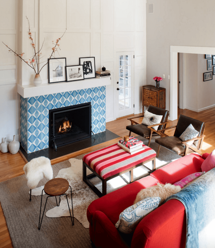 manteau cheminée en carrelage bleu et blanc type credence en mosaique dans salon avec murs blancs et décoration scandinave sur sol parquet
