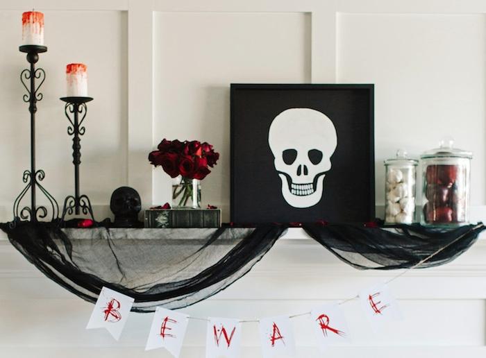 deco halloween maison avec cadre dessin crâne, bougies blanches décorées de cire rouge imitation sang sur bougeoirs noirs, voiles noire, potirons et roses décoratives
