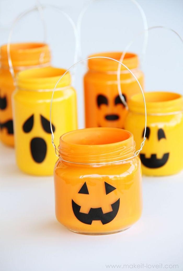 photophore halloween diy en pot de verre décoré de peinture et motif jack o lantern avec une manche en fil metallique