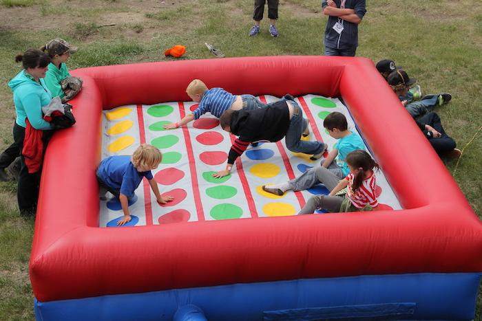 idée comment jouer au twister en plein air dans une twister gonflable avec des points colorés sur l herbe, anniversaire 5 ans