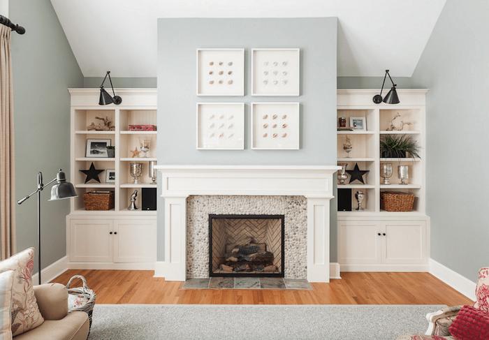 photo déco salon scandinave sur sol parquet aux murs gris clair avec cheminée manteau blanc simple et cadre en petits galets, cadres blancs carrées