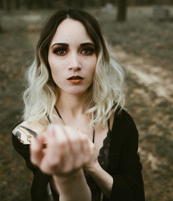 cheveux ombré blond, maquillage de sorcière, ombres orange et marron, rouge à lèvres orange, gilet noir et top dentelle