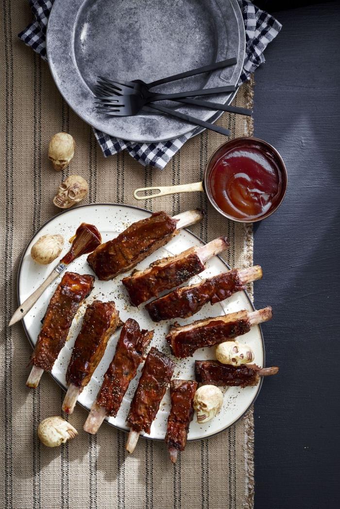 recette d'halloween plat principal de côtelettes grillées à la sauce barbecue et leur présentation effrayante imitant une cage thoracique