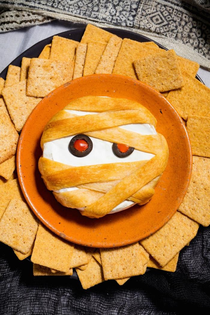 recette de brie cuit au four avec une croûte de bandelettes de pâte feuilletée façon momie d'halloween, recette d'halloween effrayante pour un apéro