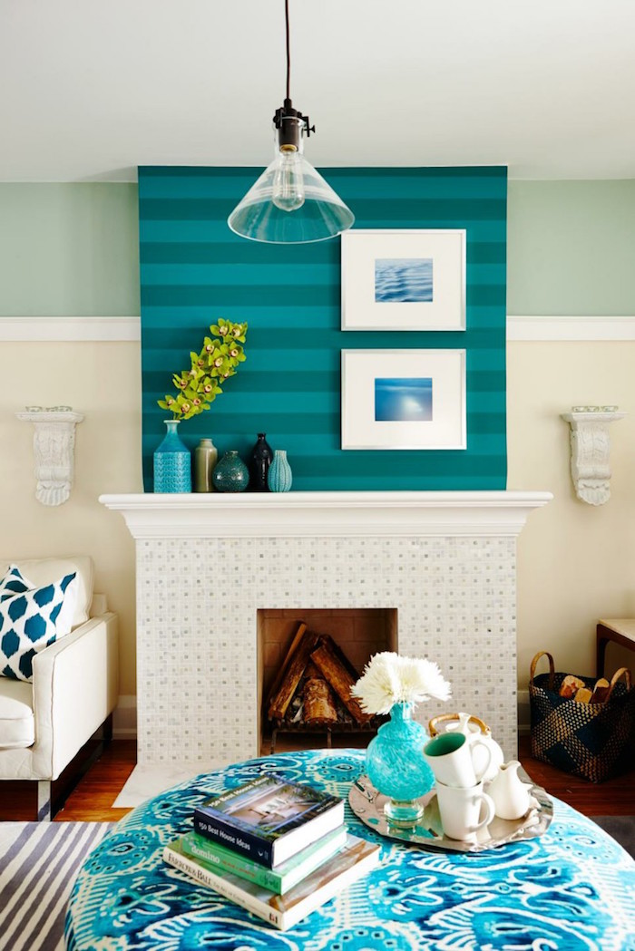 décoration de cheminée avec manteau blanc large sous mur bleu à rayures et cadres blancs avec photos d'ocean, table de salon ronde bleu et blanc