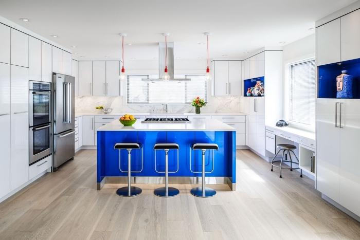 modèle d'îlot central tendance bicolore en blanc et bleu électrique avec tabourets de bar en argent, modèle cuisine blanche avec parquet bois clair