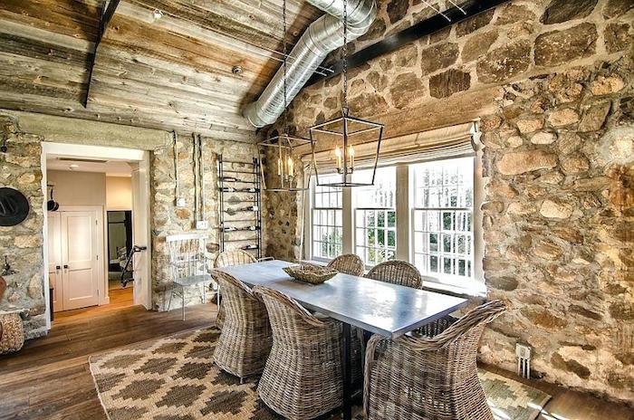 intérieur de ferme cottage rénovée avec mur en pierres et plafond arqué en bois style scandinave