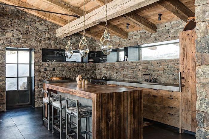cuisine de ferme rénovée avec mur en pierre apparente interieur et charpente en bois d'origine