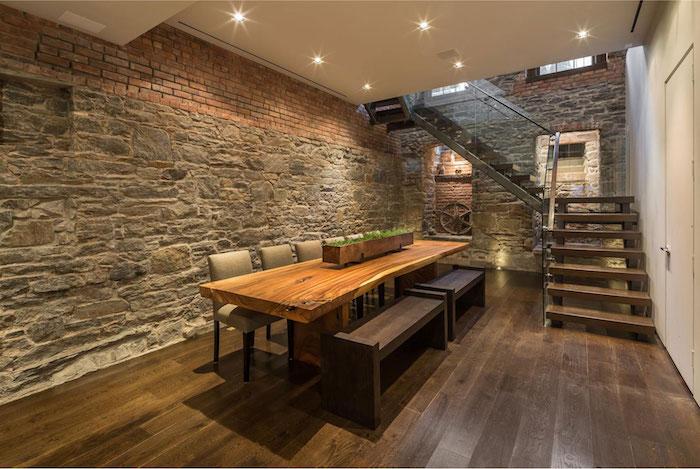 rez de chaussée de loft aménagé avec murs en pierres et briques sur sol en parquet brun