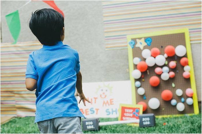 exemple de jeu de tir pour enfant sur des ballons colorés posés sur un tableau en bois, jeux anniversaire 7 ans