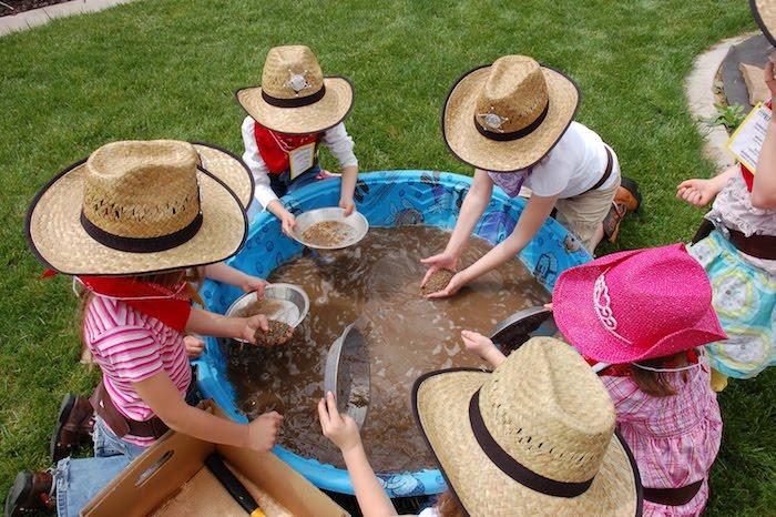 idée originale de jeu inspiration western, chasse à l or, enfants déguisés en cow boy qui pêchent de l or dans une piscine gonflable à la boue