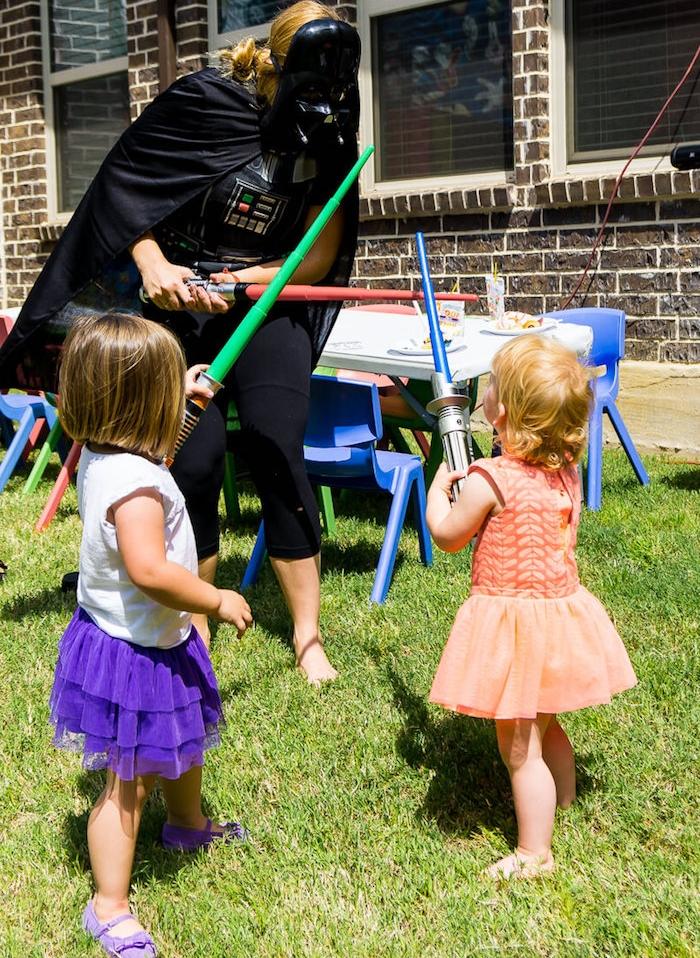 idée d anniversaire star wars, aniamteur déguisé en dark vador, petites filles en robes de princesse, anniversaire enfant en plein air