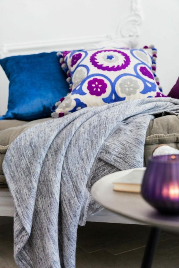 lit en lilas et bleu, grande couverture grise, table ronde, peinture murale blanche, porte bougie lilas