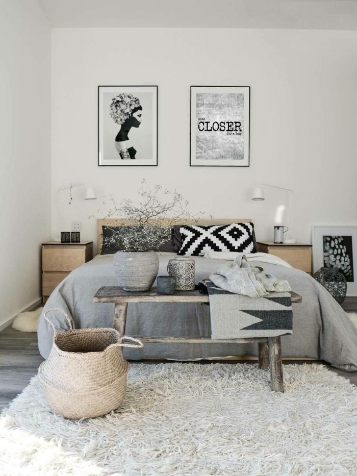 lit cosy, couverture de lit grise, banquette en bois, panier en rotin, tapis gris moelleux, coussin imprimé ethnique, peintures monochromes, chambre rustique