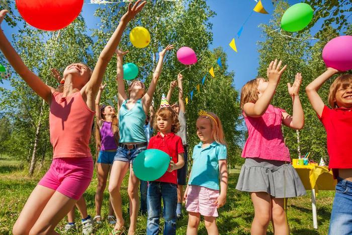 jouer avec des ballons d anniversaire colorés sur un gazon, gouter d anniversaire enfant avec des enfants d ages variés