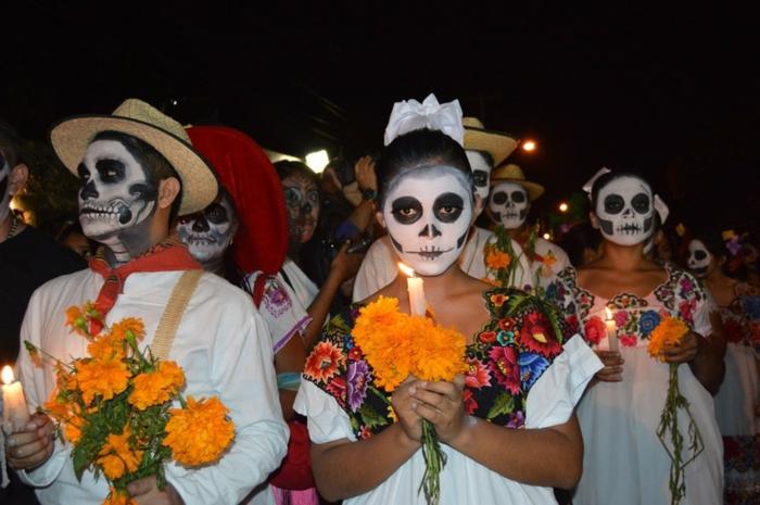 la fête des morts en Mexique, mexicains habillés pour la fête, bouquets jaunes, bougies allumées et maquillage tete de mort