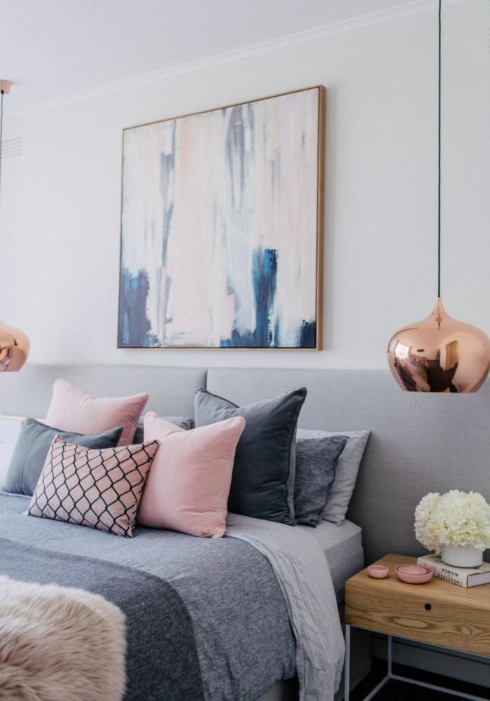 deco cocooning, coussins en rose et gris, tableau abstrait, deux lampe pendante finition cuivrée, chevet en bois