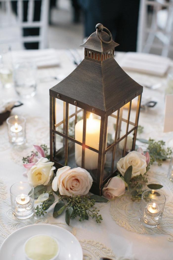 table de mariage joliment décorée, lanterne métallique, bougie blanche, roses et bougies flottantes