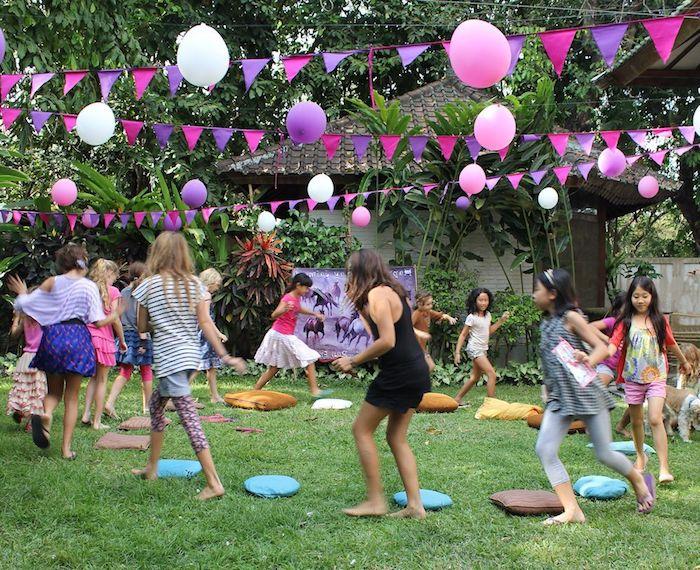 le coussin musical sur un gazon à l extérieur avec des enfants, decoration anniversaire guirlande à fanions et ballons colorés, anniversaire 9 ans