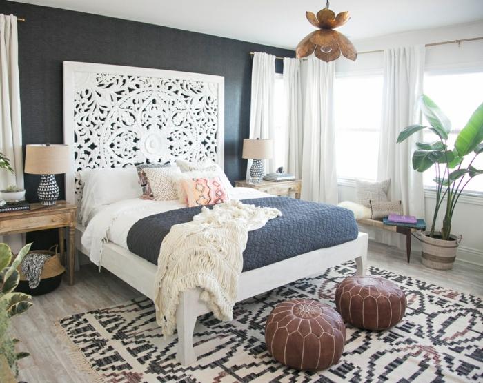 lit blanc, tapis traditionnel, tabourets en cuir, grande plante verte, deux tables de chevet en bois