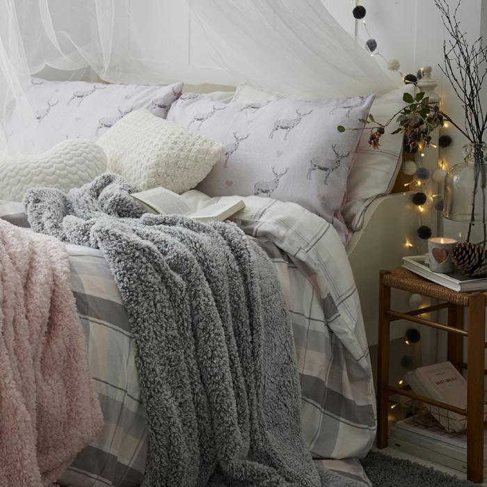 guirlandes de petites boules et de lampes électriques, coussins blancs, plaids fausse fourrure couleurs pastels, voilage blanc, petit tabouret rustique