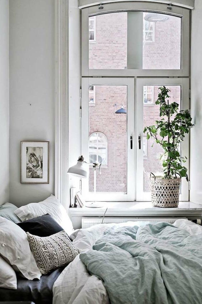 lit cosy dans une chambre blanche et lumineuse, cache-pot rustique, cadre peinture gris et blanc, plante verte, lampe de table blanche