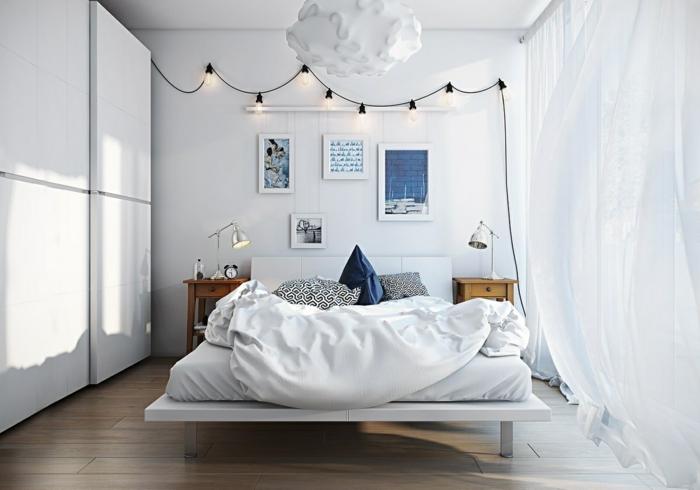 suspension nuage, guirlande d'ampoules, lit flottant blanc, sol en bois foncé, deux chevets en bois, coussins