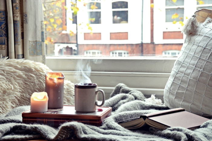 rideau géométrique, grande fenêtre, bougies allumées, tasse de café chaud, coussin et plaid gris