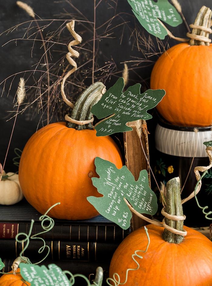 citrouilles avec feuilles artificiels avec des textes sur une pile de livres anciens, activités manuelles halloween originales