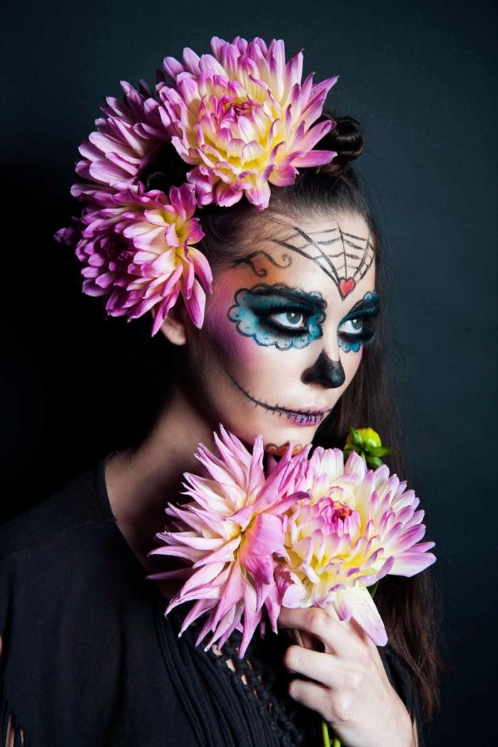 jolie tête de mort mexicaine réalisée avec un mélange de fard noir, bleu turquoise, rose et orange, maquillage squelette facile façon poupée cadavérique