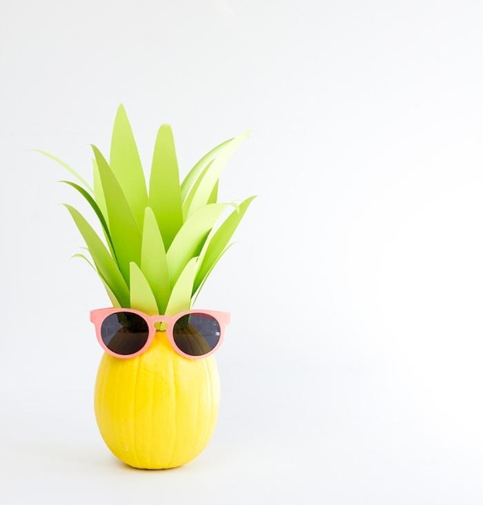 courge halloween à design ananas peint en jaune avec déco en papier cartonné vert découpé en formes de feuilles vertes