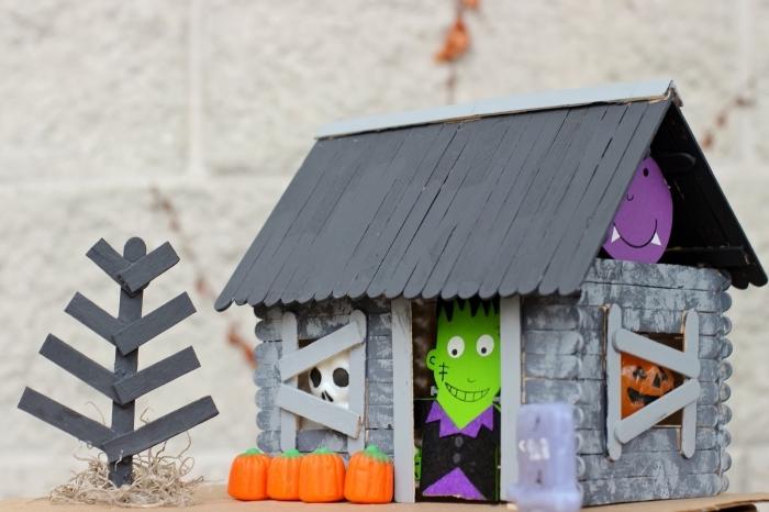 bricolage halloween maternelle avec des bâtonnets de glace en bois, fabrication d'une maison hantée avec des bâtonnets de glace et des personnages d'halloween découpés en carton