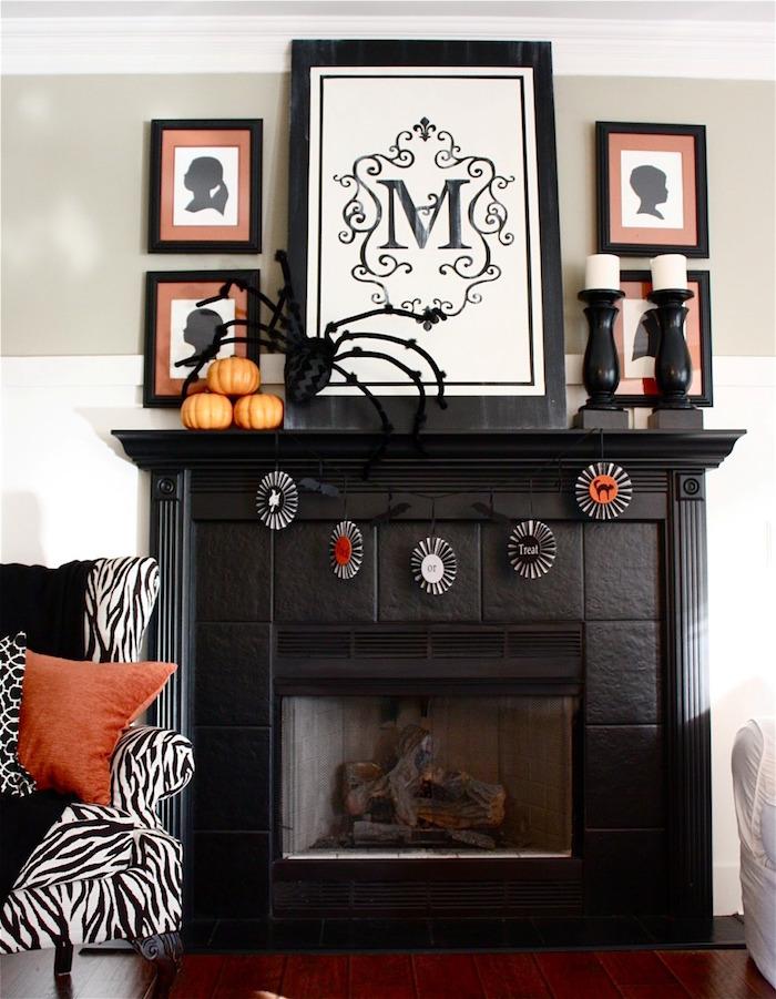 cheminée noire mat avec cadre en carrelage et déco halloween orange avec mini citrouilles, cadres dessins silhouette et canapé zébré