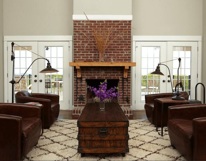 salon à déco vintage avec fauteuils en cuir foncé, table en bois ciré type malle et manteau de cheminée en briques rouges avec étagère en bois