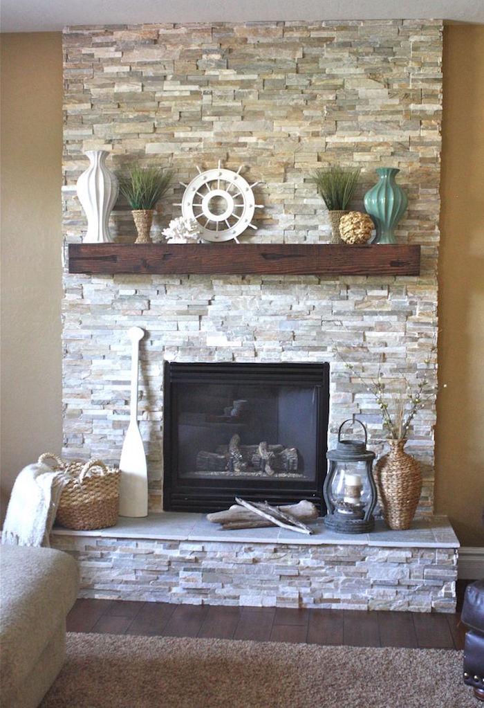 déco rustique rétro pour cheminée dans mur en pierres de parement sur mur taupe